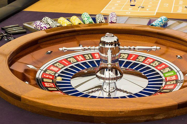 Wooden roulette wheel with chips beside the wheel.